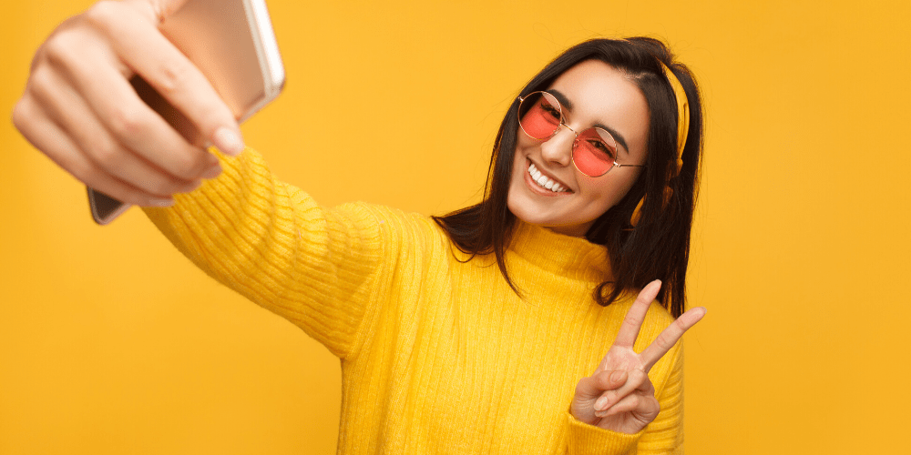 girl in yellow taking a selfie-min
